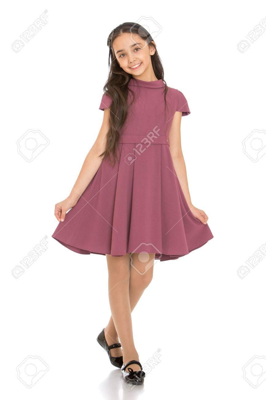 0ea4fe4a762b Archivio Fotografico - Elegante giovane ragazza dai capelli scuri in età  scolare a lungo alla moda Vestito svasato-isolato su sfondo bianco