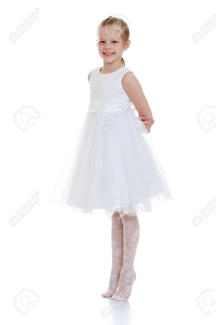 ziet er geweldig uit gerenommeerde site gedetailleerde look Heel mooi meisje in een lange witte jurk ballet met zijn handen achter zijn  rug staande op tenen-Geïsoleerd op witte achtergrond