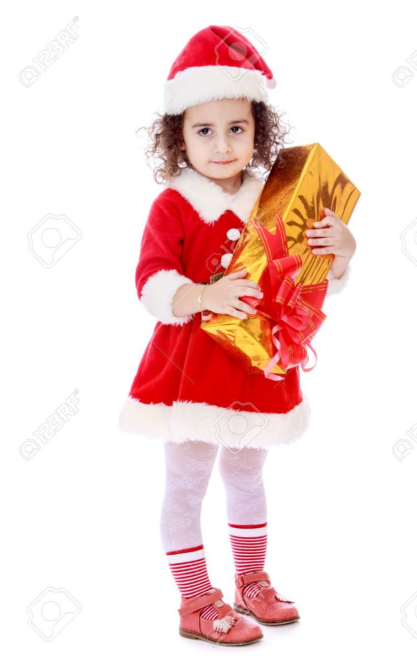 very cute little curly girl in a suit and cap of santa claus.. stock