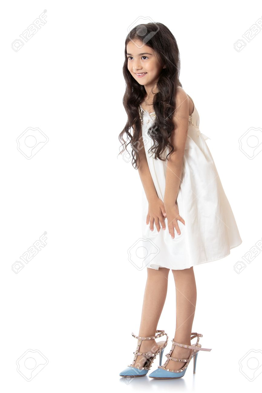 Elegant, slim little girl of Eastern appearance, with long dark hair, trying on mom's high-heeled shoes. Shoes on the feet of the girls are very large - Isolated on white background - 49208974
