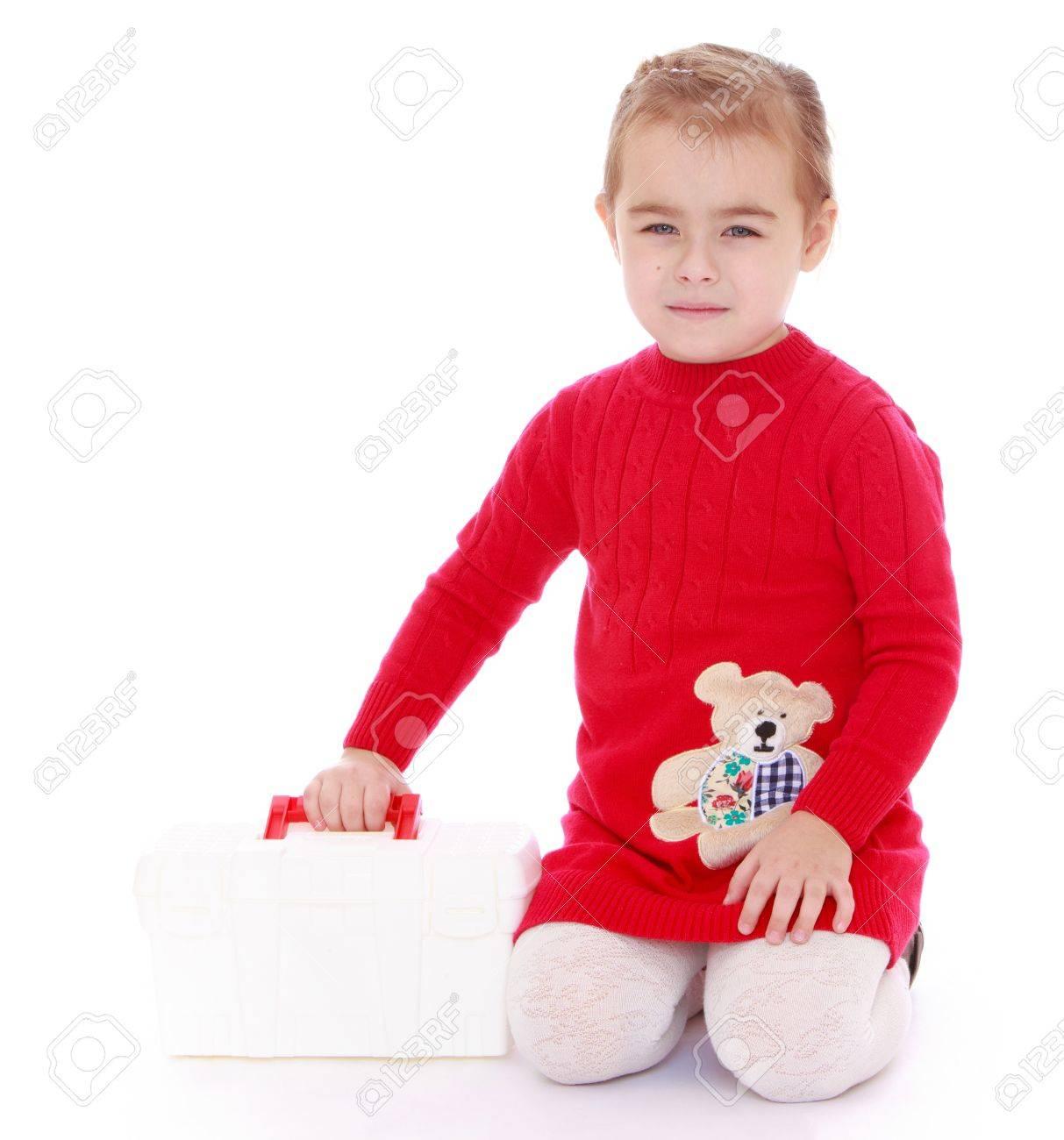 online retailer 63985 555e8 Bambina sveglia in un vestito lavorato a maglia rosso è in ginocchio, e  tiene la sua mano una valigetta medica bianco - isolato su sfondo bianco