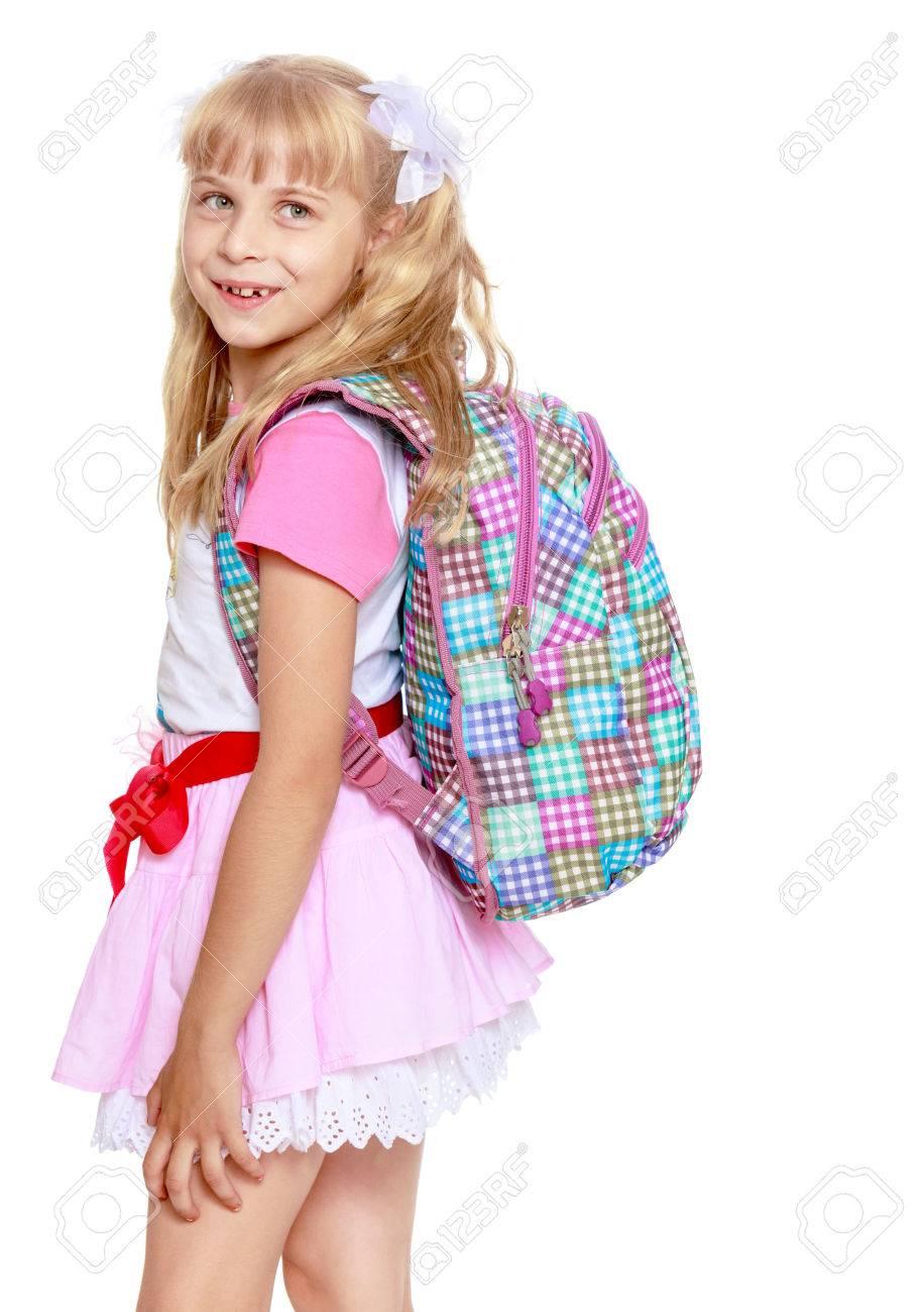 5439c62ba562d Banque d images - Enthousiaste petite fille dans une jupe courte rose avec  un sac à dos sur ses épaules. Close-up-isolé sur fond blanc
