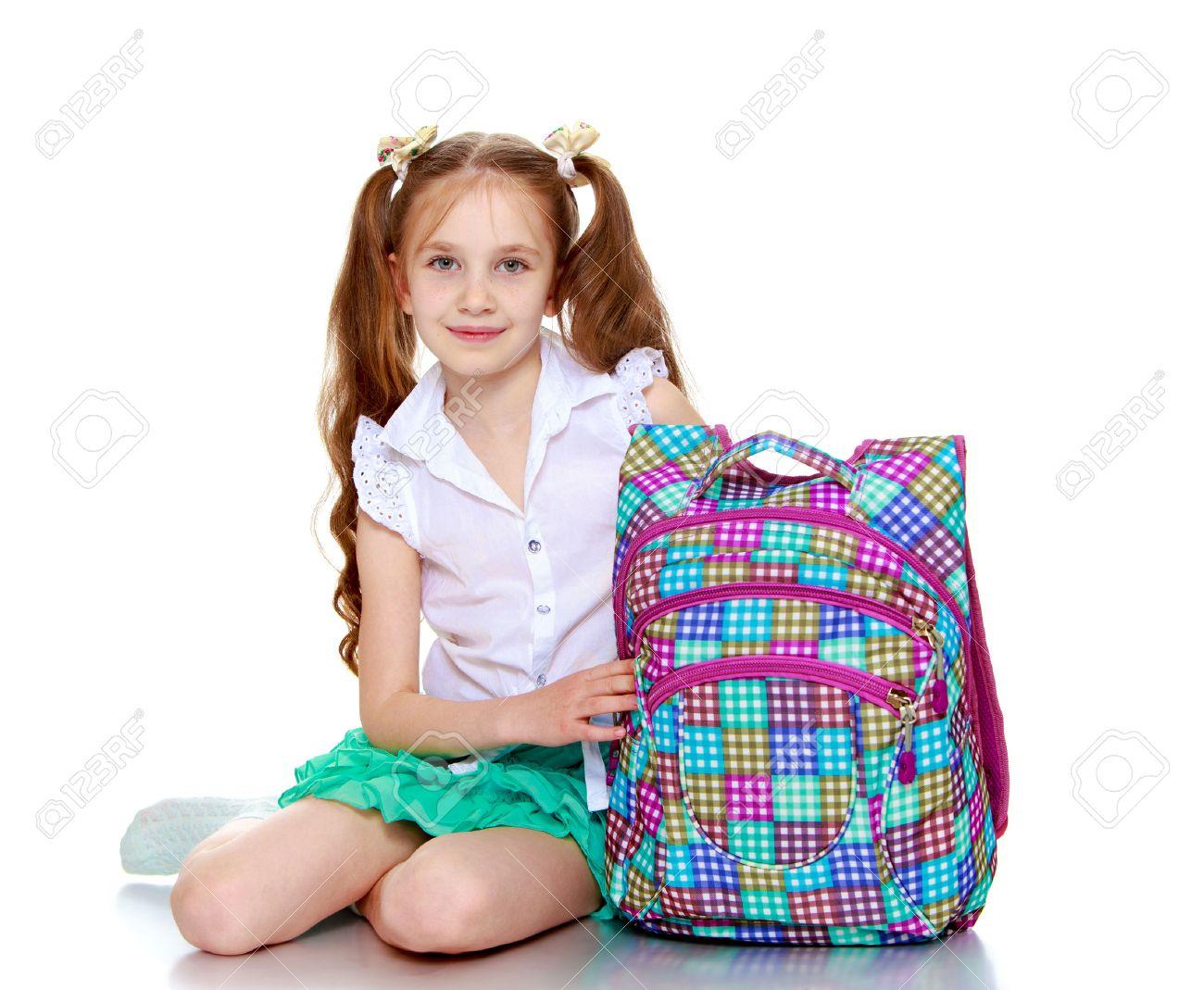 65c17267efb374 Leuk meisje in een korte groene rok en witte blouse met een  schooltas-Geïsoleerd op