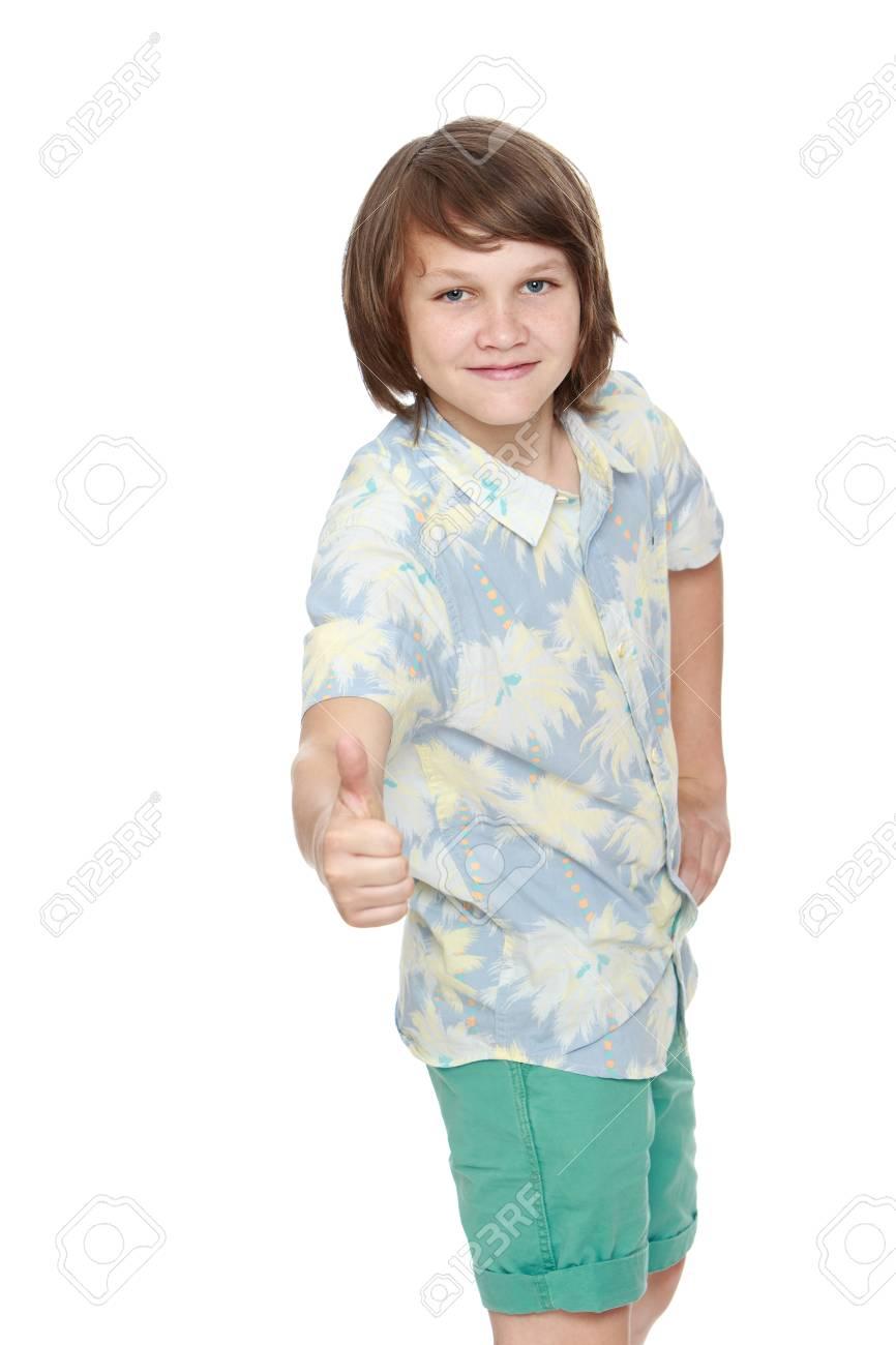 Ritratto di un ragazzo sorridente in pantaloncini e camicia con le maniche corte. Il giovane alzò il pollice verso l'alto. Primo piano isolato su