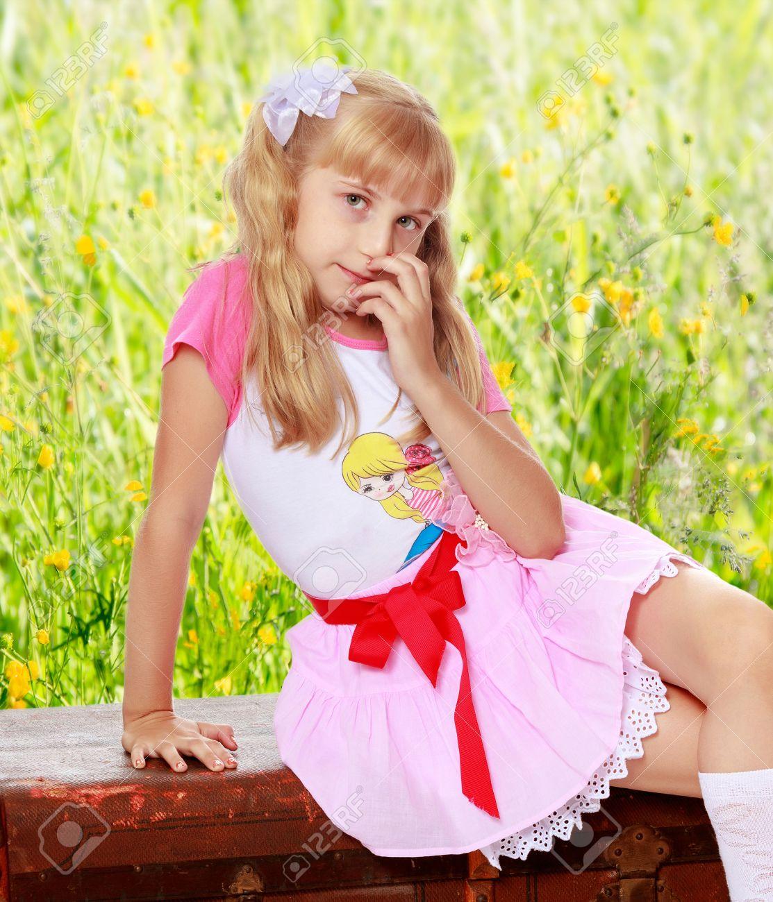 ce42b5e958 Niña Hermosa En Una Falda Corta De Color Rosa Y Medias Blancas Que Se  Sientan En La Antigua Carretera Suitcase.On El Fondo De La Hierba Verde Y  Flores ...
