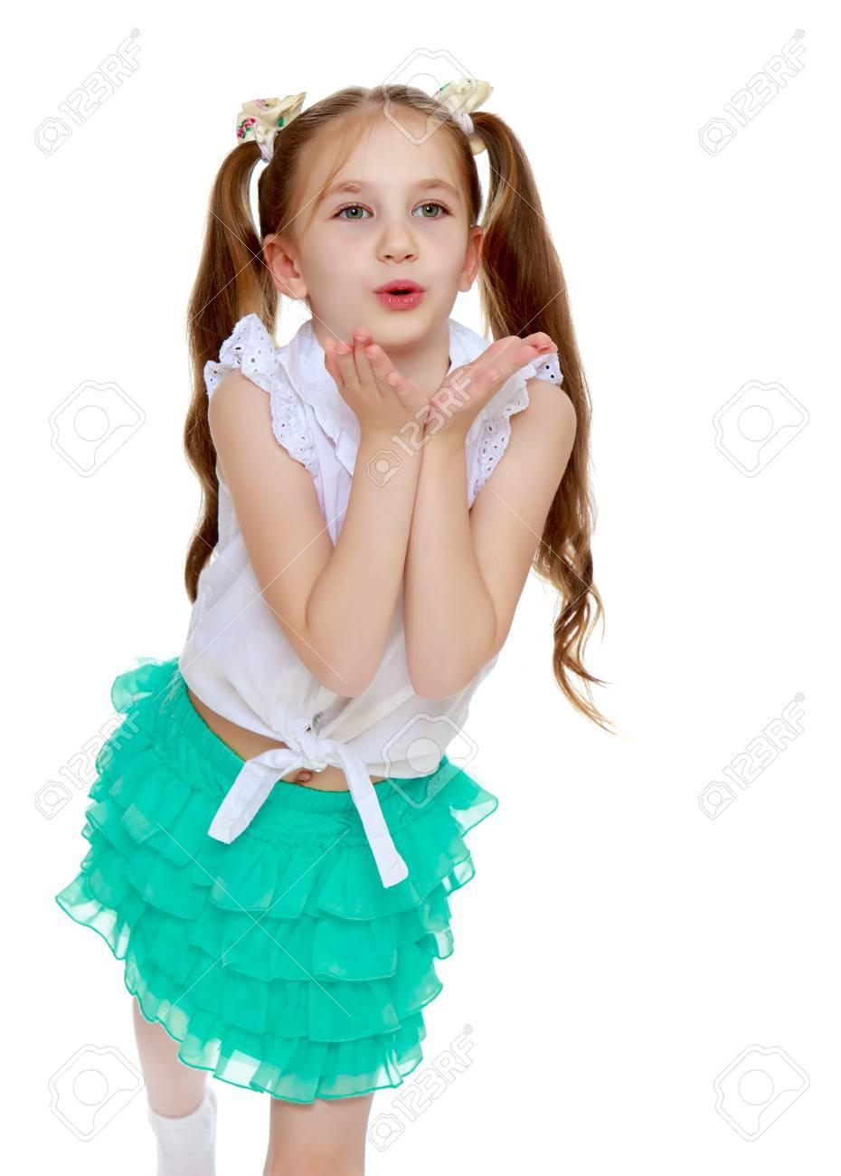 d2b8d4ef9 Niña alegre en una falda verde corta y camisa blanca sin inscripciones.  Largas colas en la cabeza en las que trenzaban cintas blancas. La chica ...
