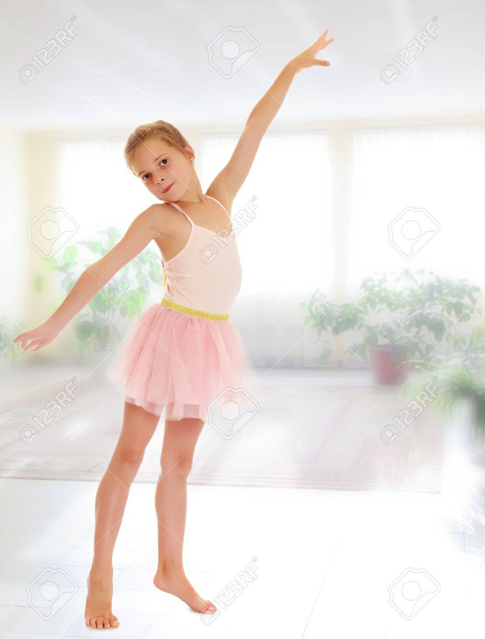 charming little girl ballerina in a pink translucent dress on