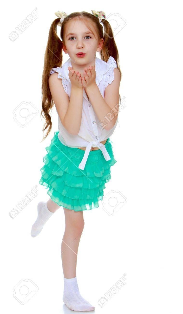 125b21f68 Niña alegre en una falda corta verde y camisa blanca sin inscripciones.  colas largas en la cabeza en el que trenzan cintas blancas. La muchacha ...