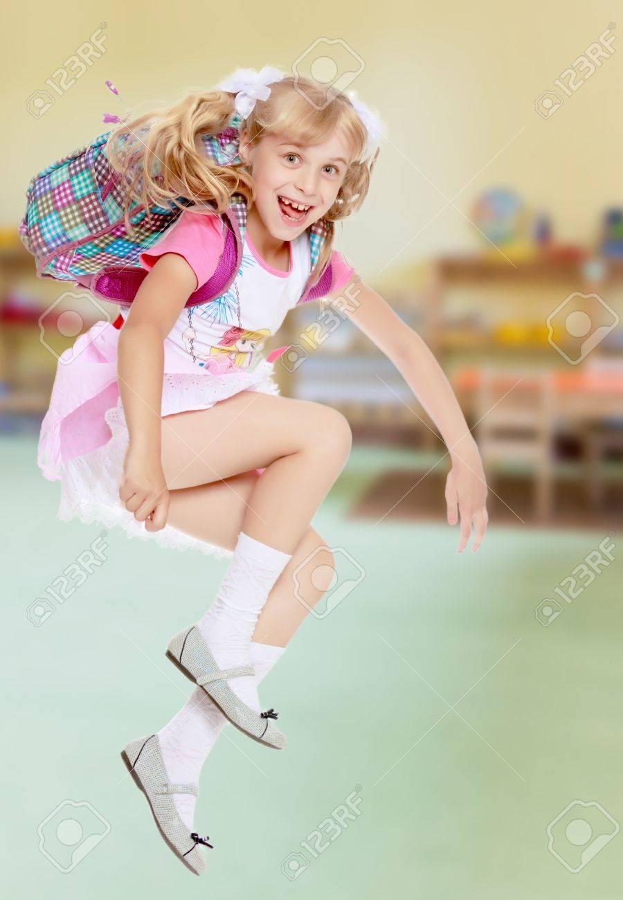 28929bc2b527d Banque d images - Enthousiaste petite fille dans un rose se précipite jupe  courte pour school.In la chambre des enfants fond où il y a des étagères  avec des ...