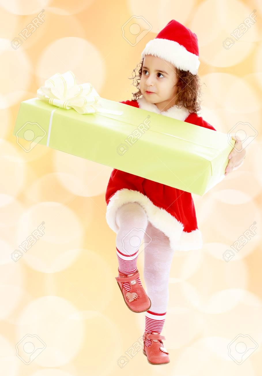 b0efafd9bf360 Cute Bambina Ricci In Un Cappotto E Cappello Di Babbo Natale Porta Il  Grande Scatola Verde. Una Ragazza Detiene Una Casella Con Il Suo Knee.