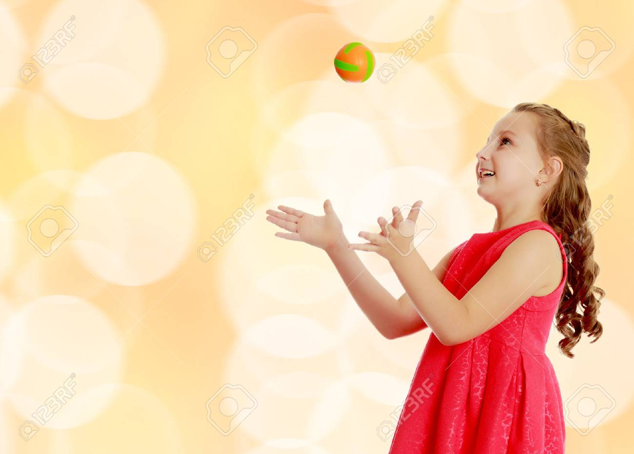Beautiful Caucasian little girl in a bright orange dress, throws a little ball.Brown festive, Christmas background with white snowflakes, circles. - 65687392
