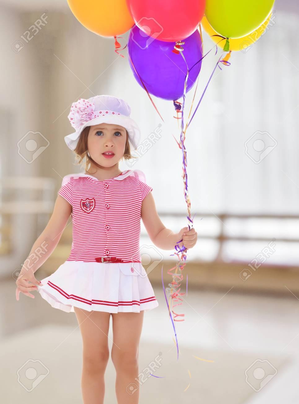Menina Caucasiano Segurando Balões Coloridos Uma Garota Em Um Vestido Rosa Curto E Um Chapéu Branco Com Laço Rosa No Fundo Do Salão Com Uma Grande