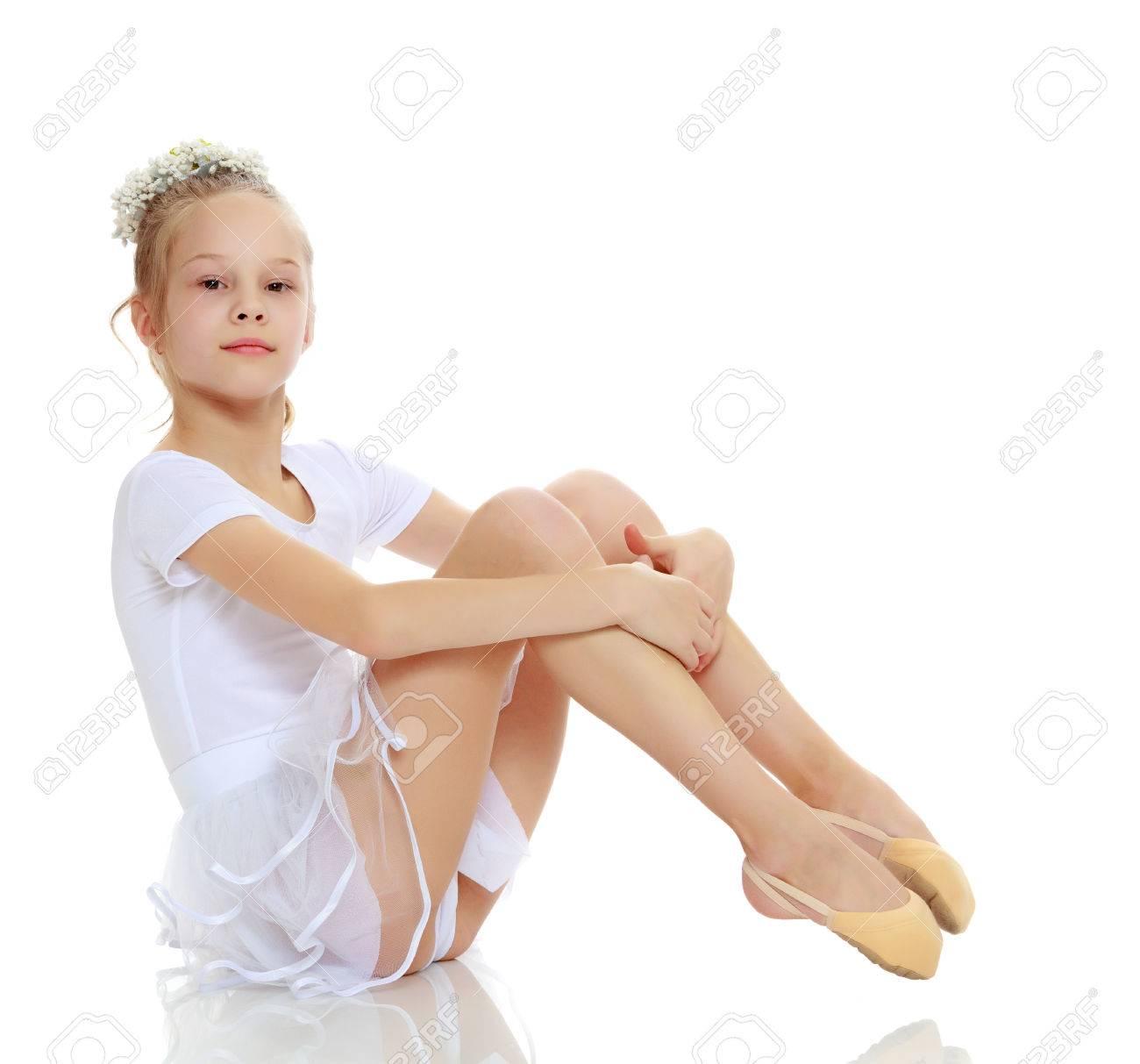 Girl gymnast posing sitting on the floor. - 75360861