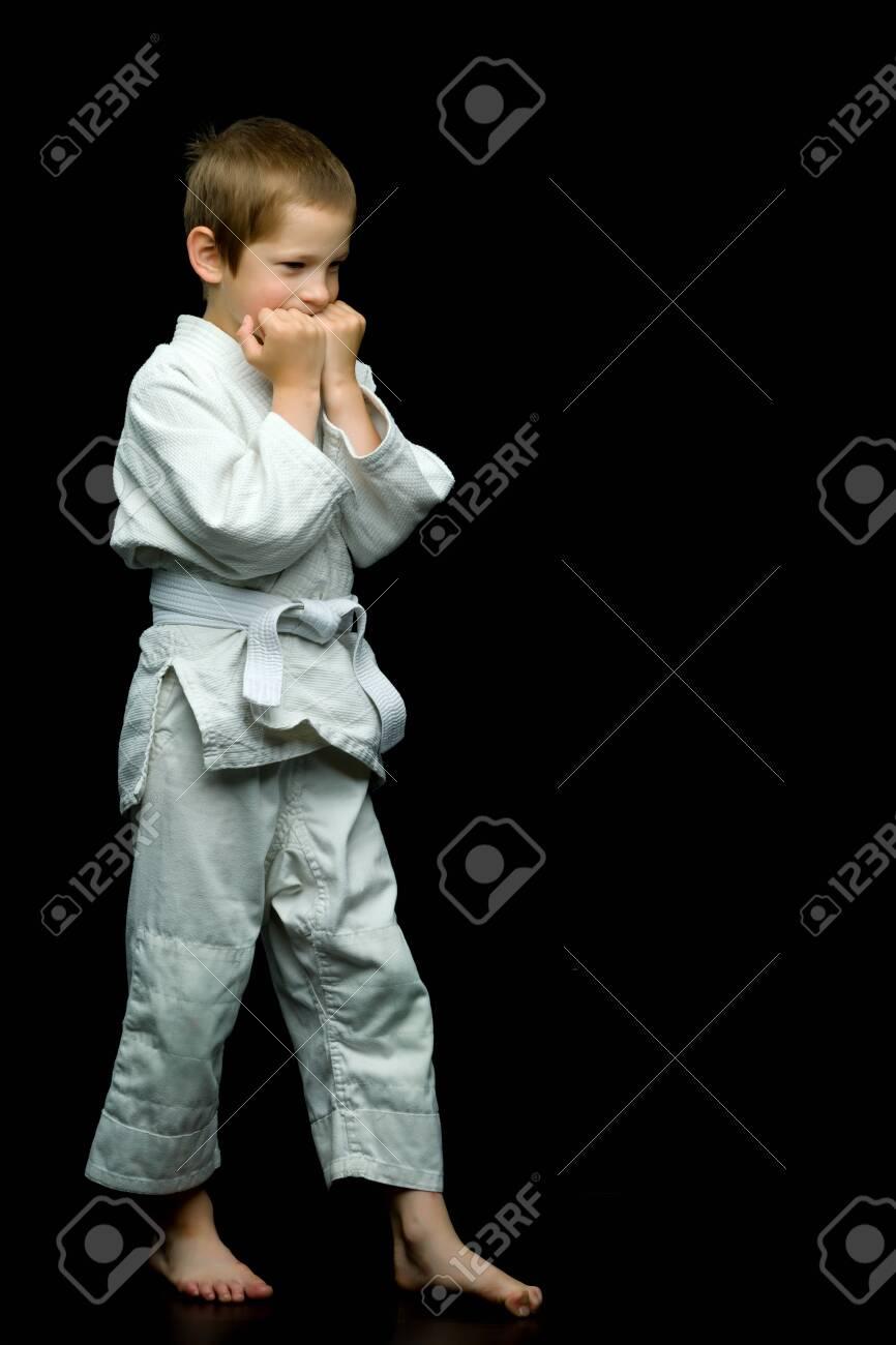 A little boy in a white kimono fulfills blows - 130867987