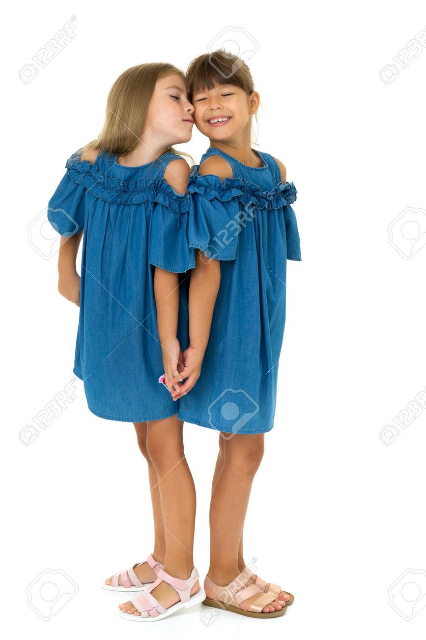 Portrait of cute girl kissing her sister on cheek - 172899425