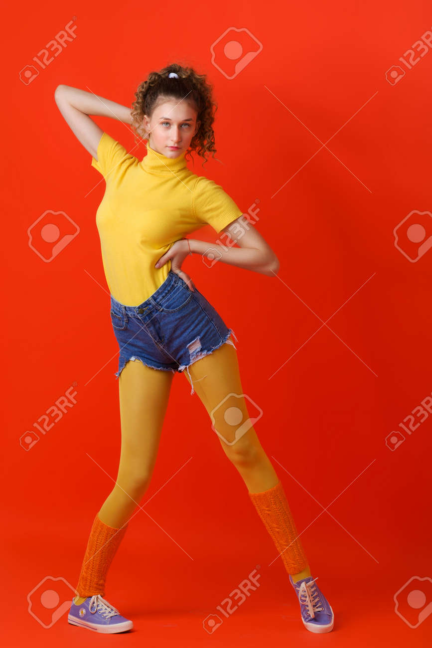 Pretty fitness girl posing relaxed on red backdrop - 173179424