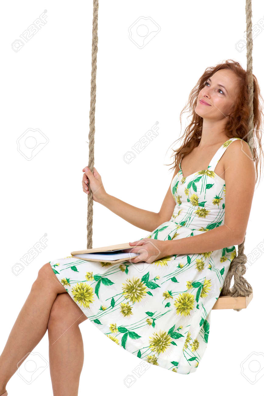 Happy young woman reading book on swing - 173027685