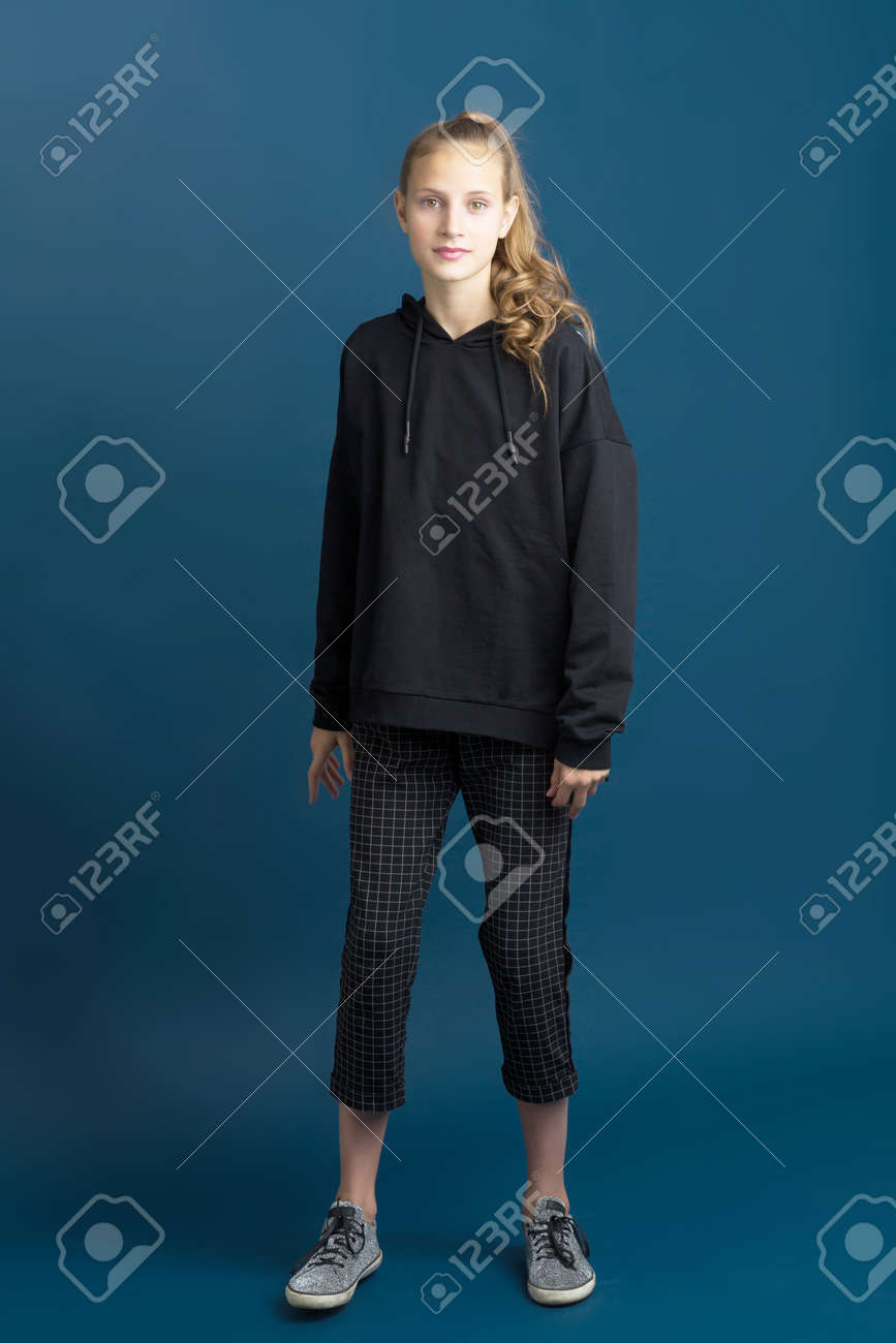 Teenage girl in black hoodie and plaid trousers - 173105280