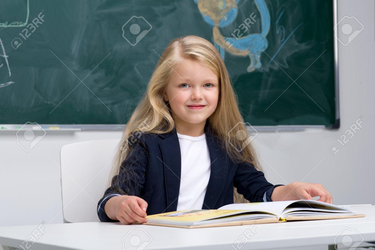 Happy schoolgirl sitting at desk - 173374397