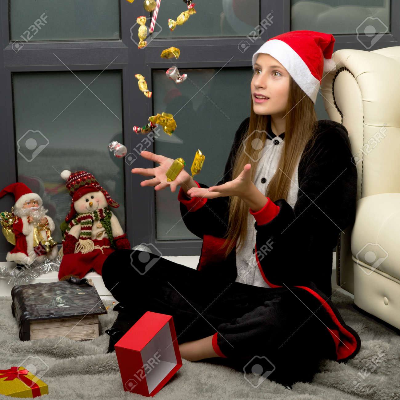 Happy girl in Santa hat throwing up candy sweets - 173438610