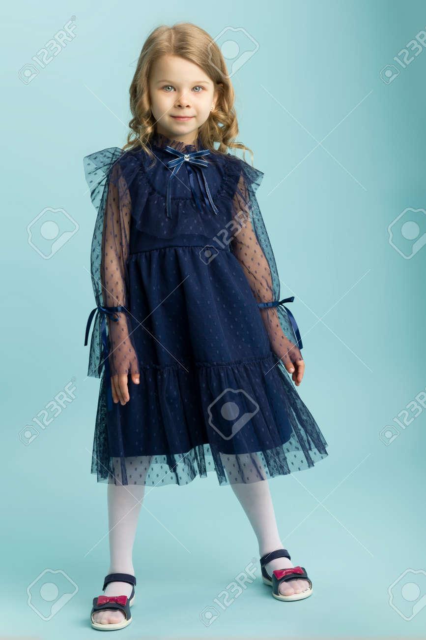 Lovely little girl posing in beautiful blue dress - 173451873