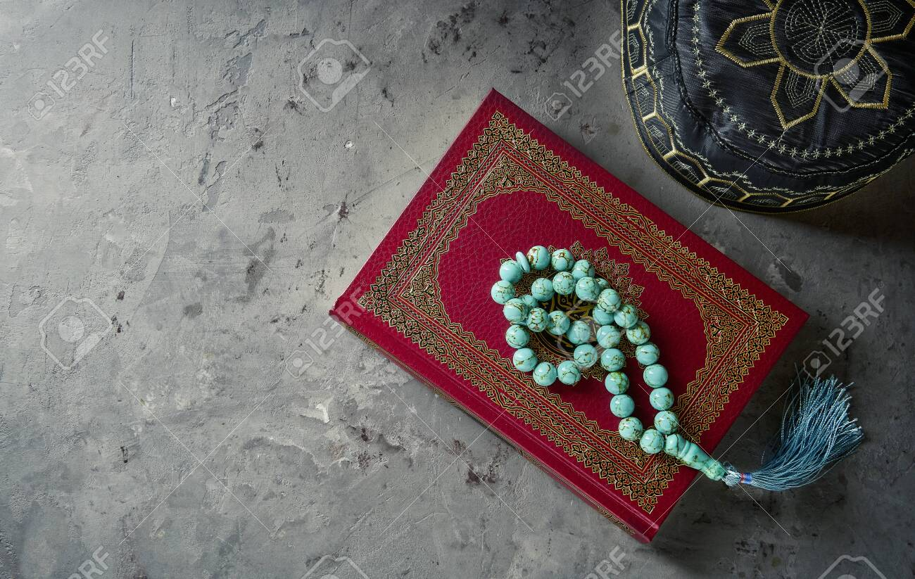 Islamic Book Koran with rosary and pray hat on grey slate background. Islamic concept with copy space - 129152594