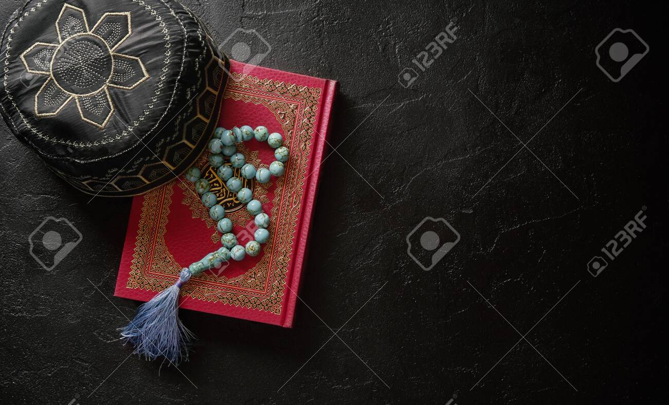 Koran with rosary and muslim hat on black stone or slate texture background. Islamic concept with copy space - 129152637