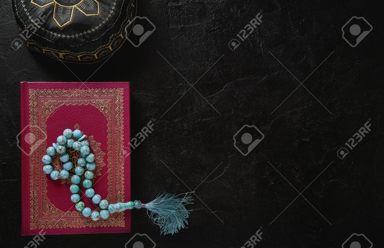 Koran with rosary beads and muslim hat on black slate texture background. Islamic concept with copy space - 129152633