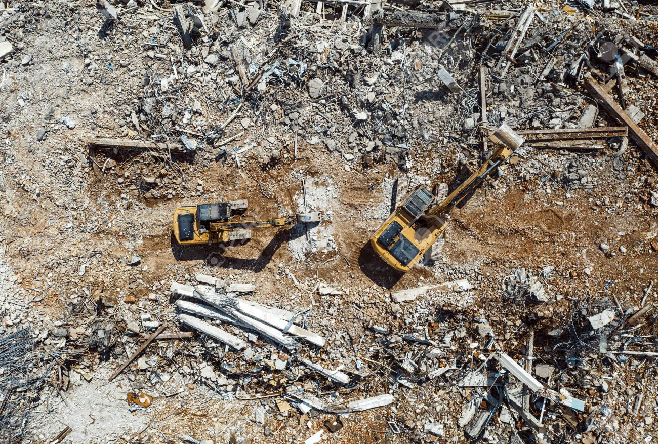 Excavators demolishing old factory for new construction project, aerial top view - 129152629