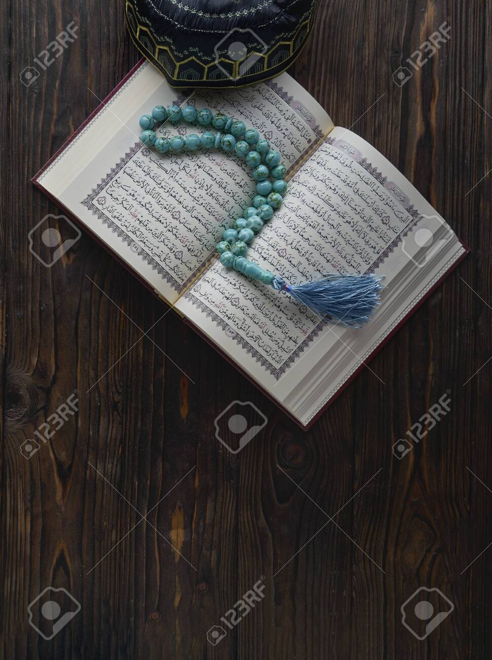 Open book Koran with rosary beads and muslim hat on wooden background. Islamic concept with copy space - 129083786