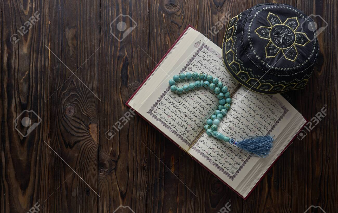 Islamic book Quran with rosary beads and muslim hat on wooden background. Islamic concept with copy space - 129083800