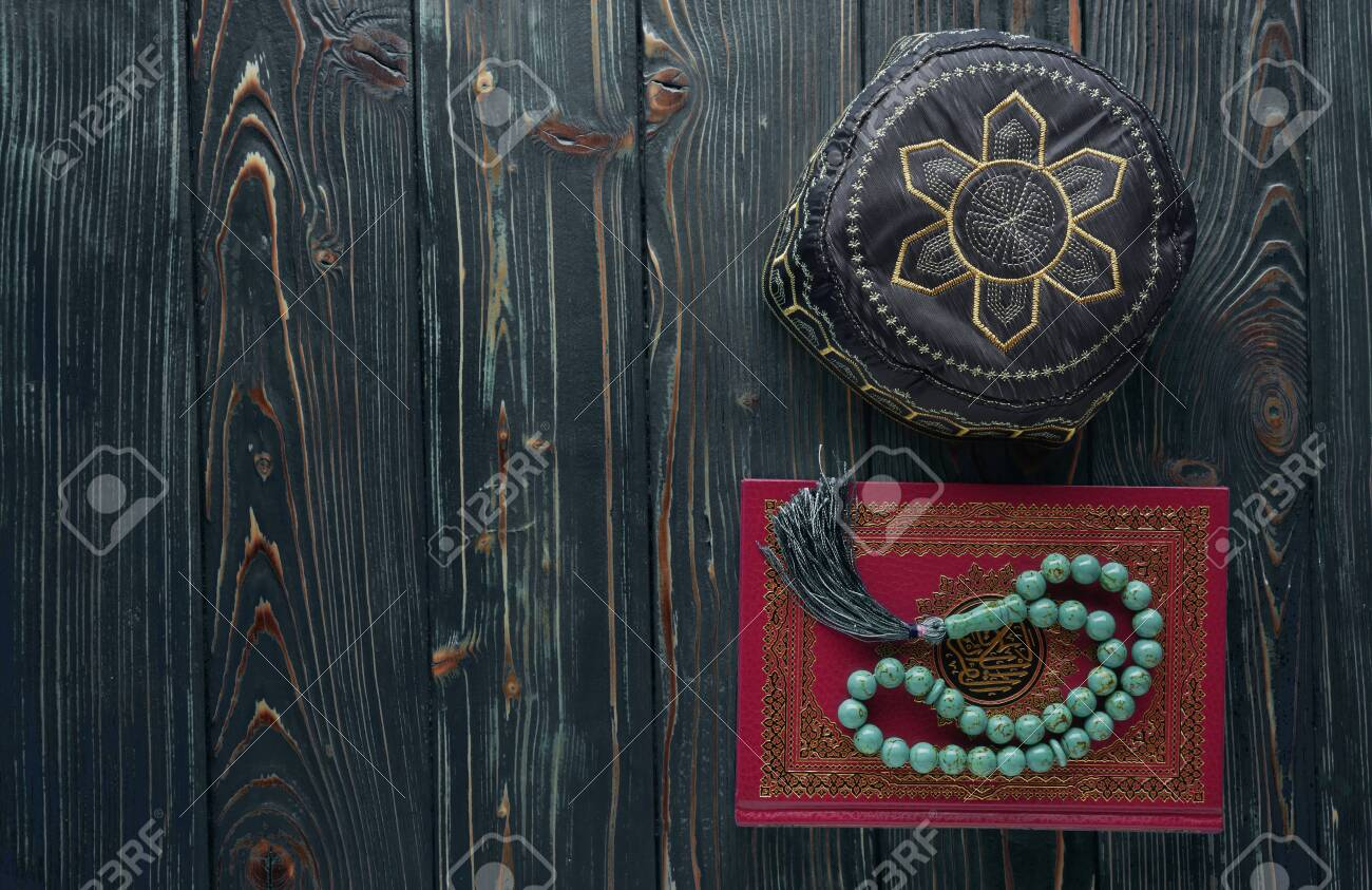 Islamic book Quran with rosary beads and muslim hat on wooden background. Islamic concept with copy space - 129083795