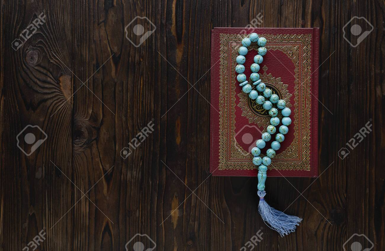 Koran with rosary beads on wooden background. Islamic concept with copy space - 129083803