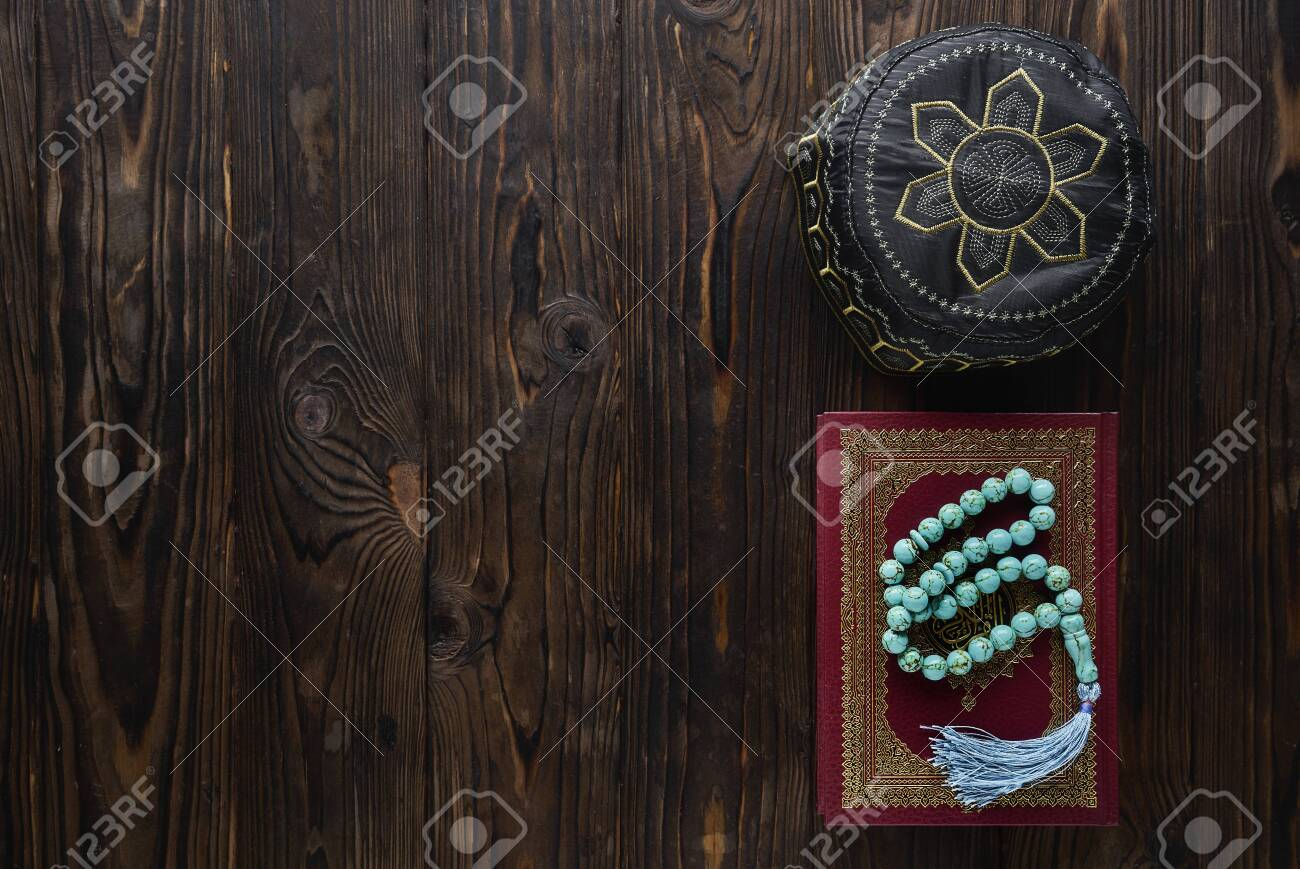 Koran with rosary beads and pray hat on wooden background. Islamic concept with copy space - 129083801