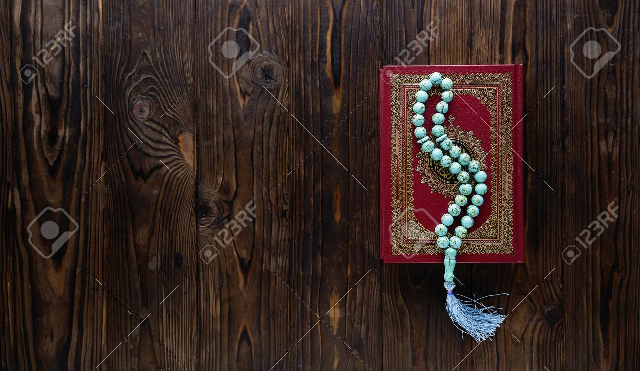 Islamic book Koran with rosary beads on wooden background. Islamic concept with copy space - 129083809