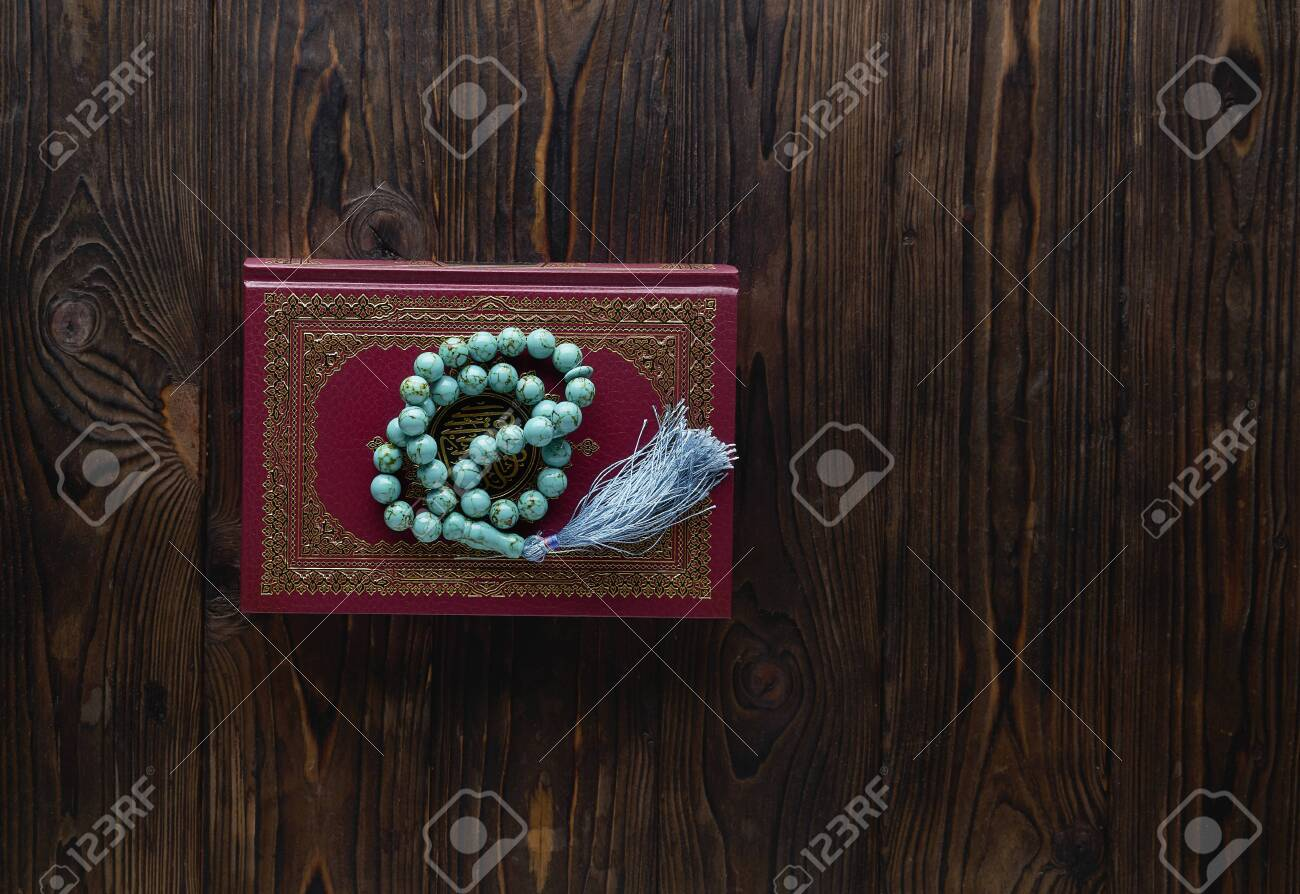 Islamic book Koran with rosary beads on wooden background. Islamic concept with copy space - 129083807
