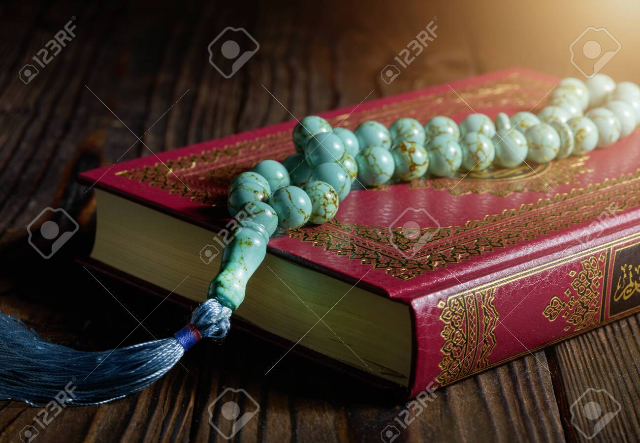 Islamic book Koran with rosary beads on wooden table - 129152616