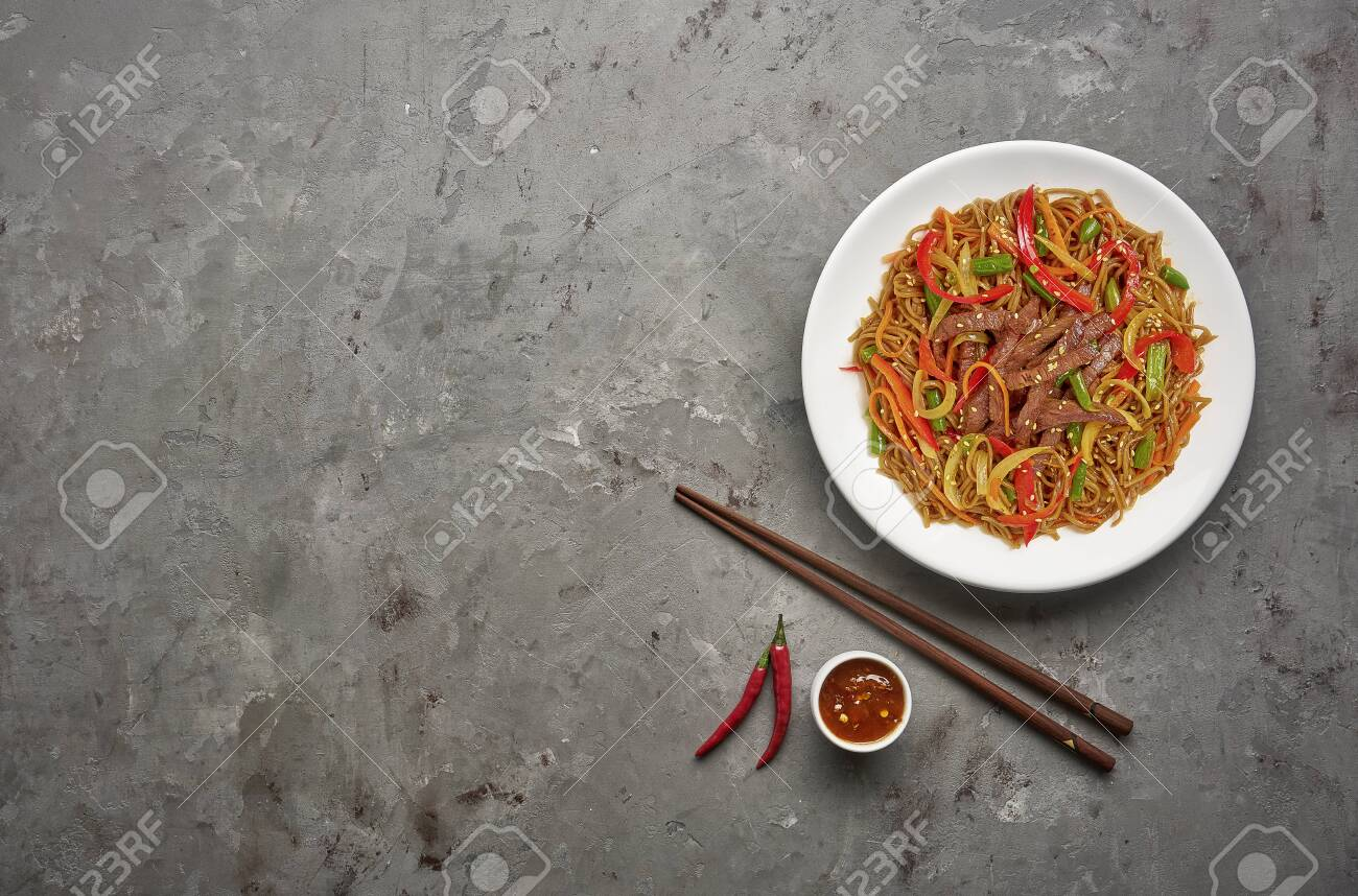 Soba noodles with beef and vegetables on grey stone background .Top view, copy space - 129154733