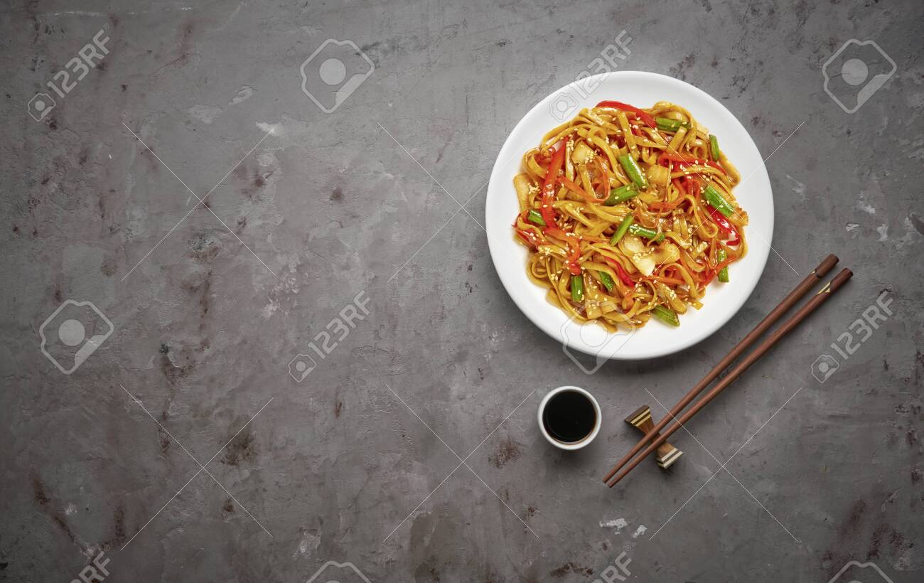 Chinese noodles with beef and vegetables on grey stone background .Top view, copy space - 129154738