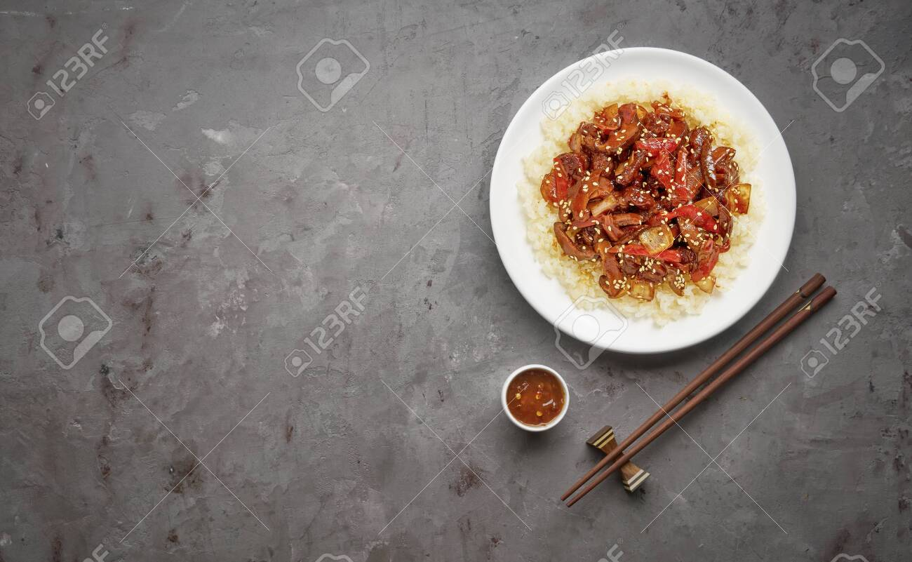 Sweet and Sour fried pork chunks with vegetables and rice on grey stone background. Top view with copy space - 129147166