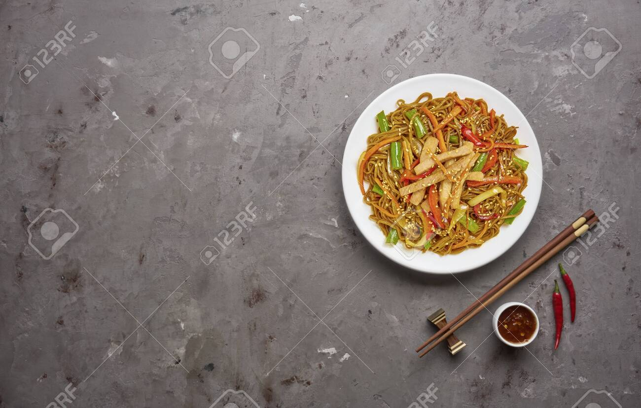 Chinese noodles with beef and vegetables on grey stone background .Top view, copy space - 129147200