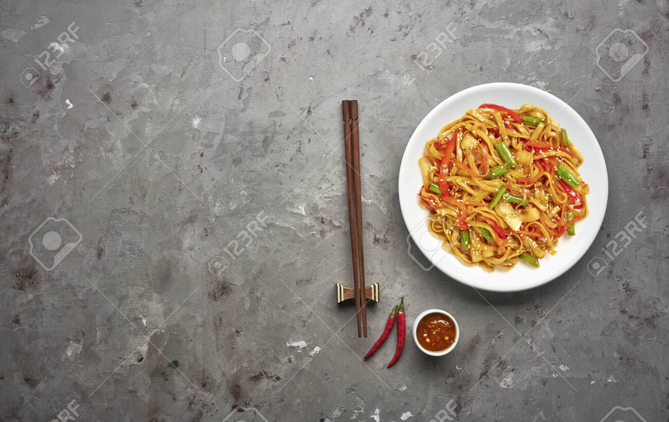 Noodles with beef and vegetables on grey stone background .Top view, copy space - 129147212