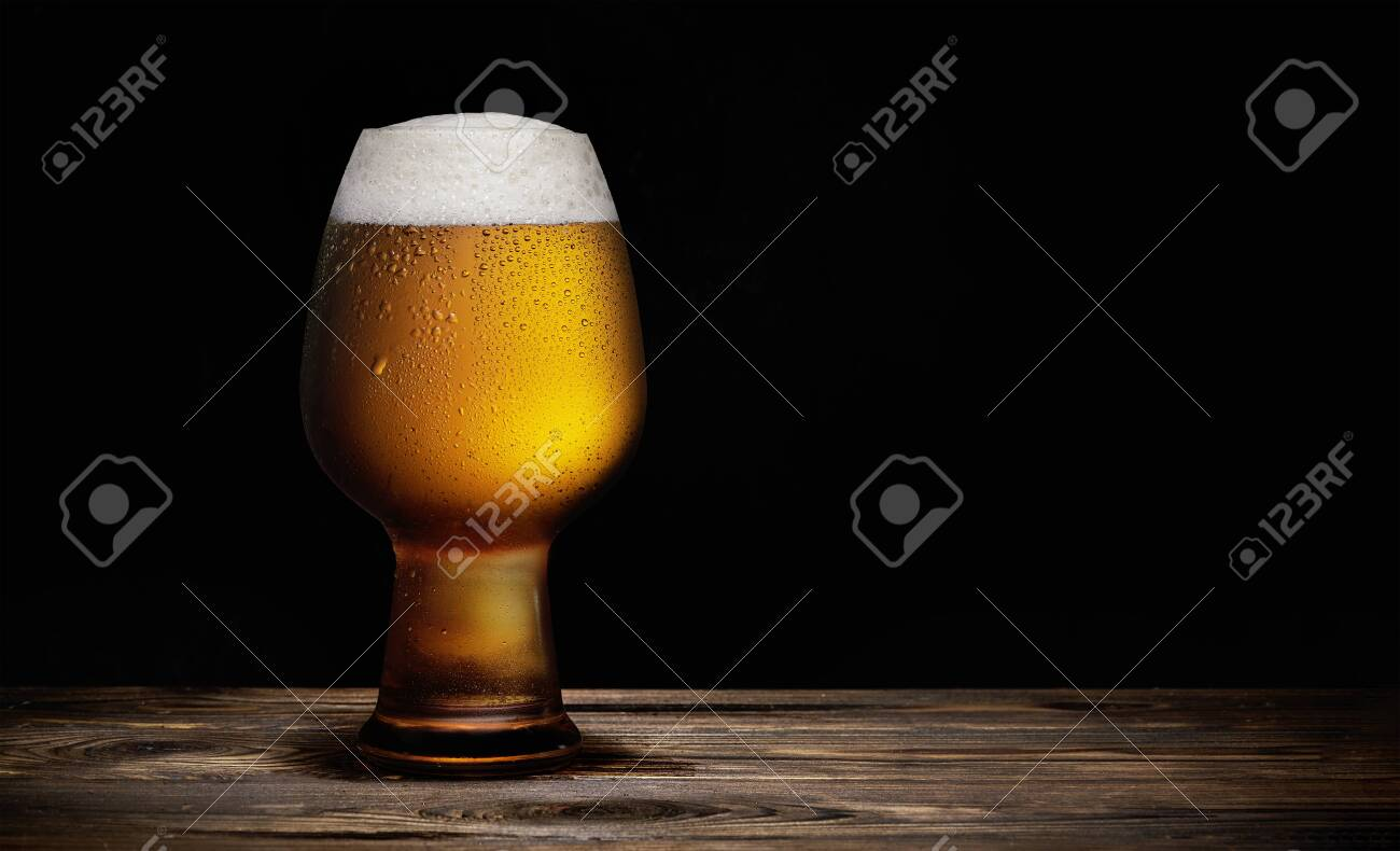 Glass of cold beer on a rustic wooden table - 129009286