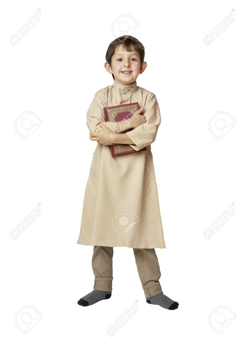 Happy muslim kid holding holy Koran on white background - 128961567
