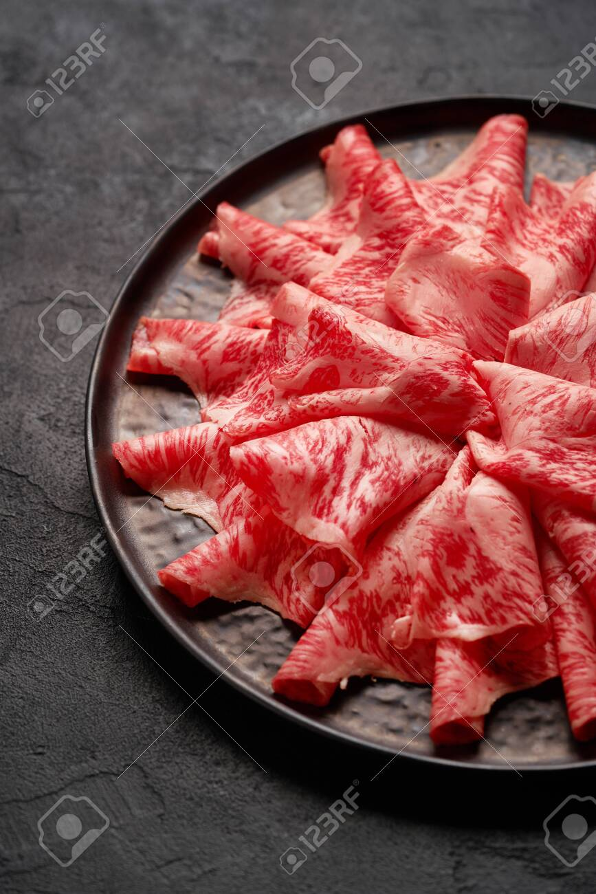 Japanese kobe beef sliced on ceramic plate on black background - 131905336