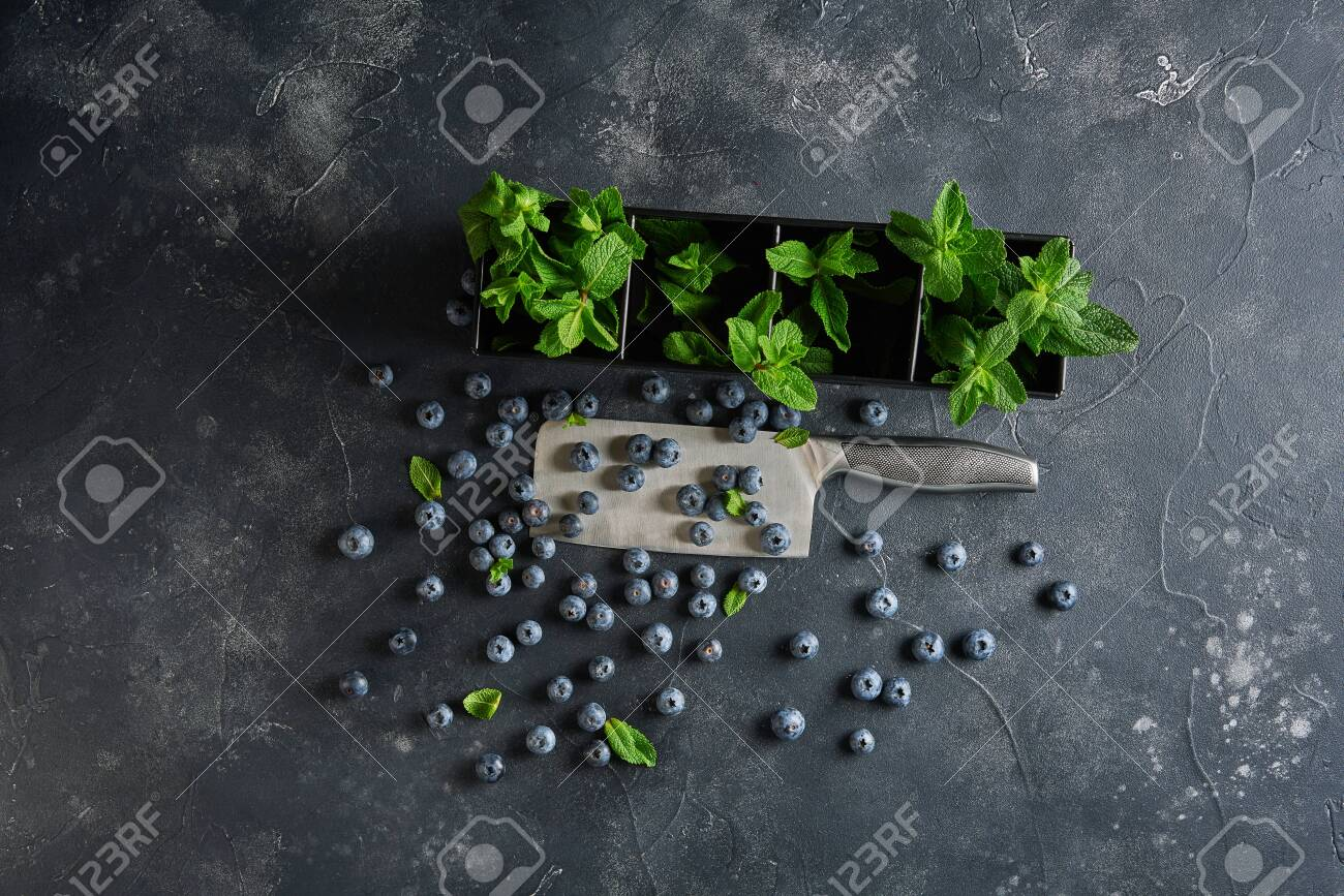 Top view of blueberries with fresh mint on dark rustic background with copy space. - 131904920