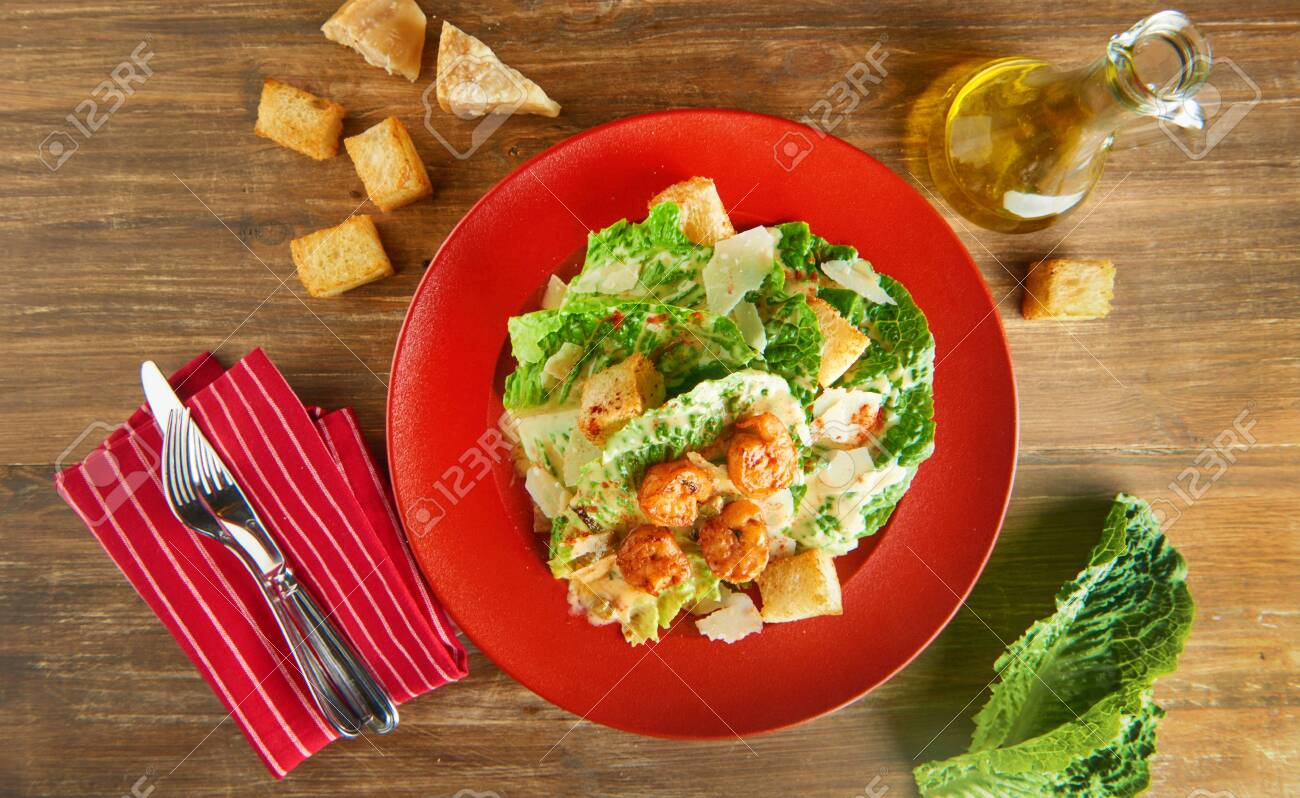 Fresh caesar salad on red plate with parmesan cheese and shrimps on wooden table. Top view - 131904945