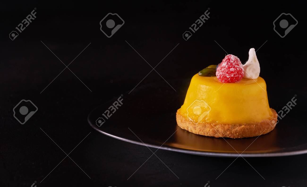 Mango mousse cake dessert covered with yellow glaze on black plate - 131905240