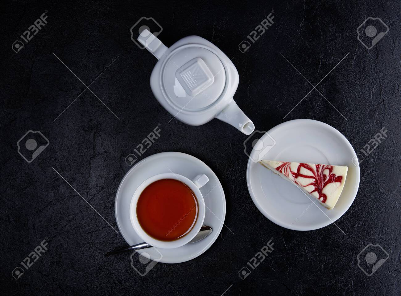 Pieces of cheesecake, cup of tea and teapot on black background. Top view, Flat lay - 131904960