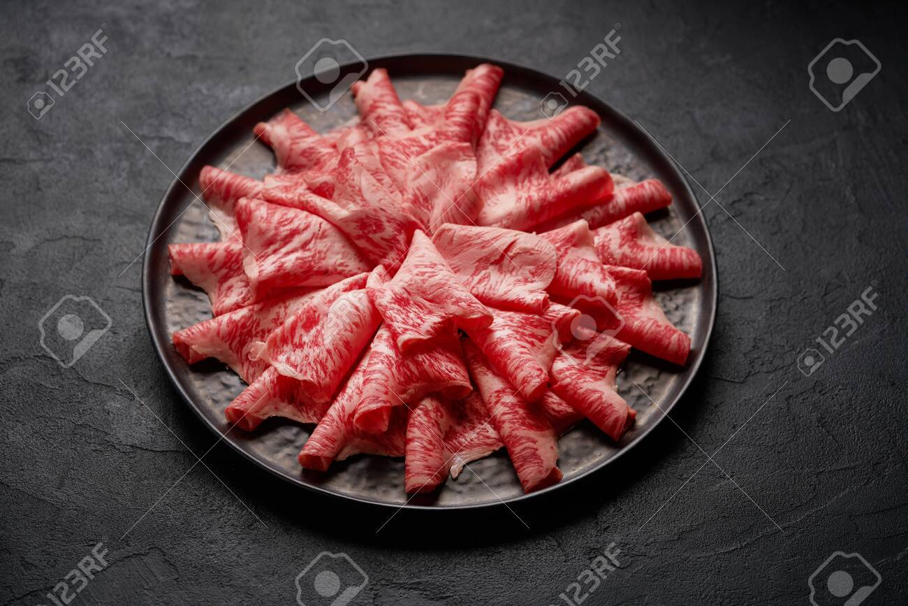 Japanese kobe beef sliced on plate prepared for shabu shabu on black background - 131905089